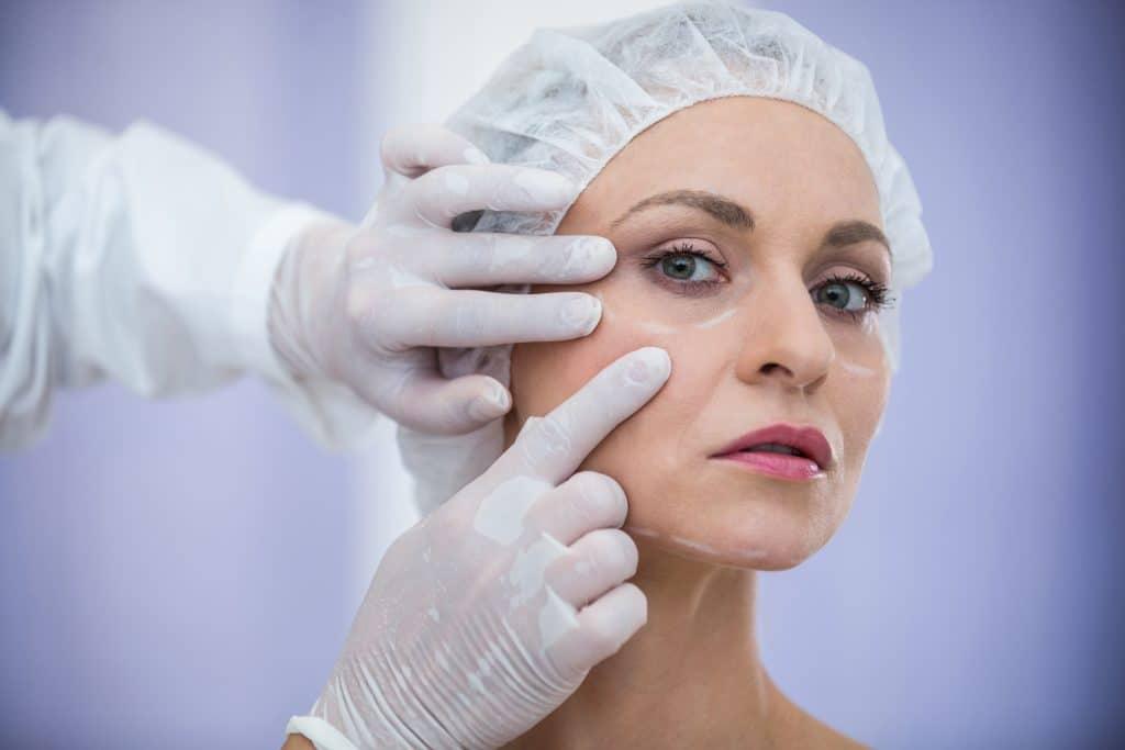 dottore esamina viso di paziente prima di un possibile lifting viso e collo
