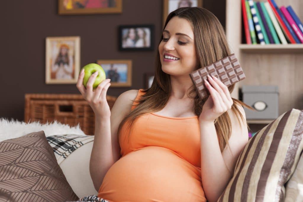 donna con mela e cioccolato in mano che si chiede cosa mangiare in gravidanza per non ingrassare troppo
