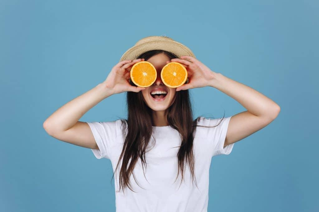 Donna felice con arance sugli occhi - dimagrire in modo sano