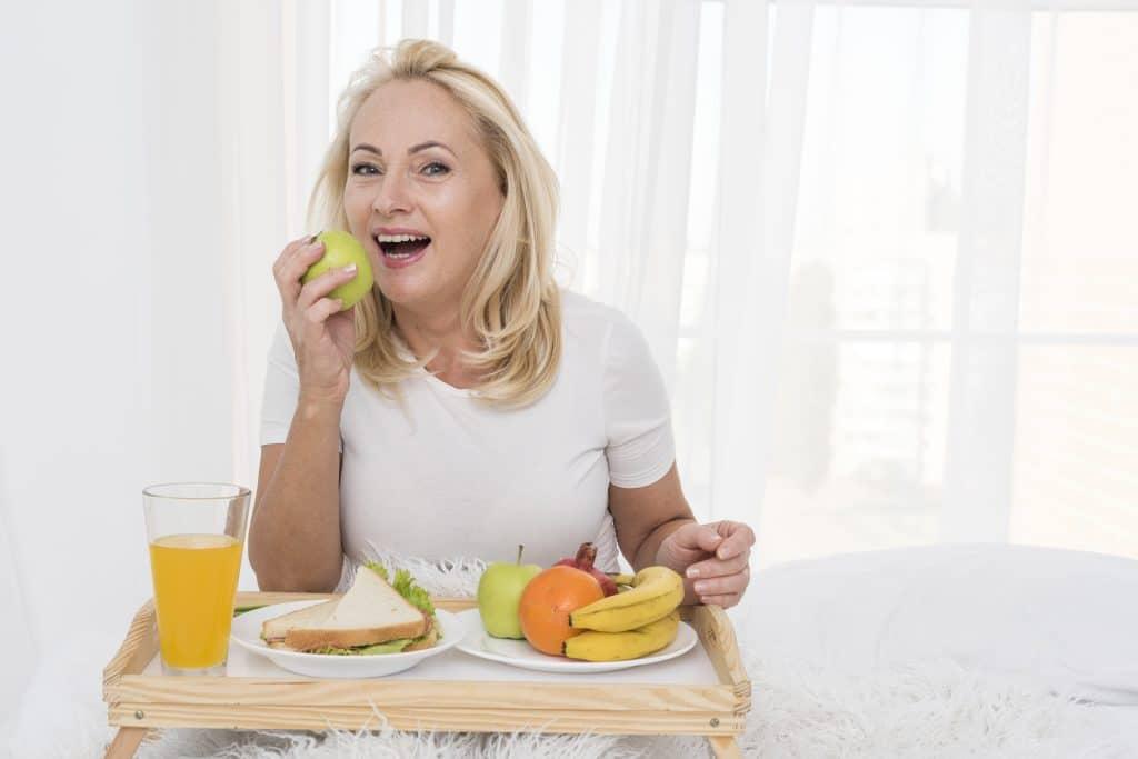 donna di mezza età che sta mangiando una mela perché segue una dieta per donne in menopausa