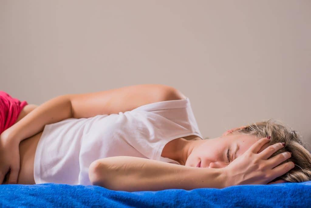 Donna sdraiata sul letto con forte dolore mestruale