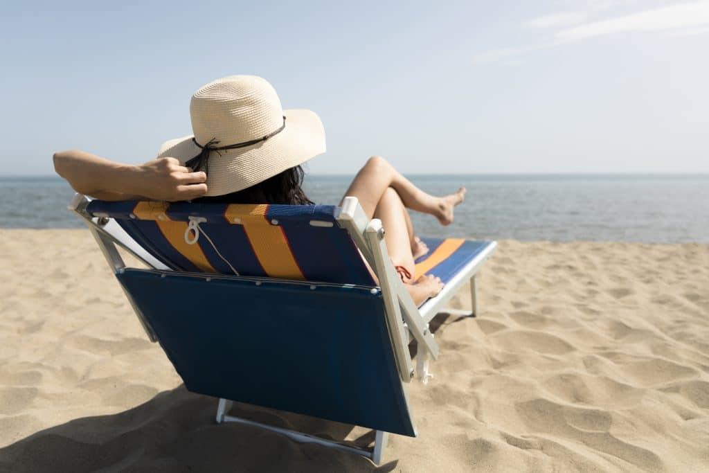 Donna sdraiata al sole con pelle nuda in riva al mare - effetti positivi e negativi sulla pelle di esposizione solare