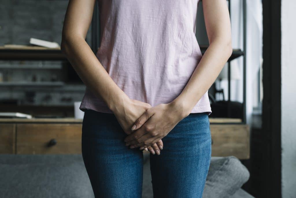 donna vestita che si protegge la zona vaginale con le mani