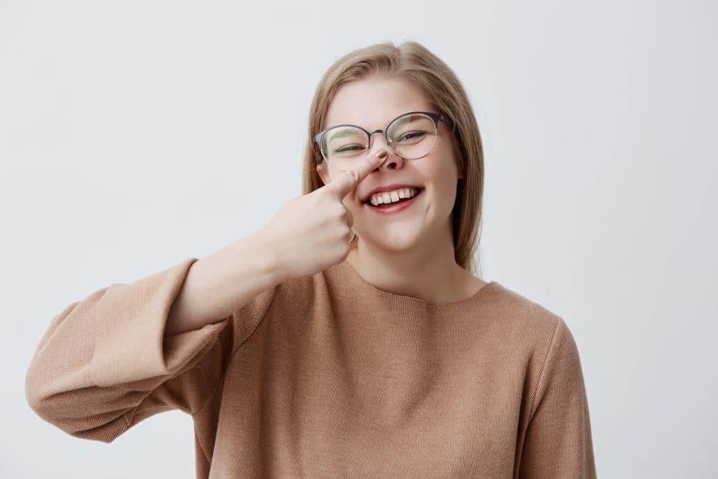 donna che si tocca il naso con un dito