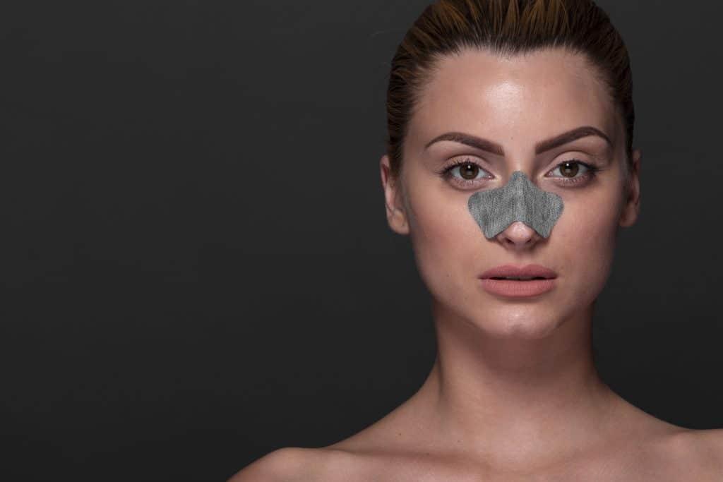 volto di donna su background scuro con cerotto sul naso