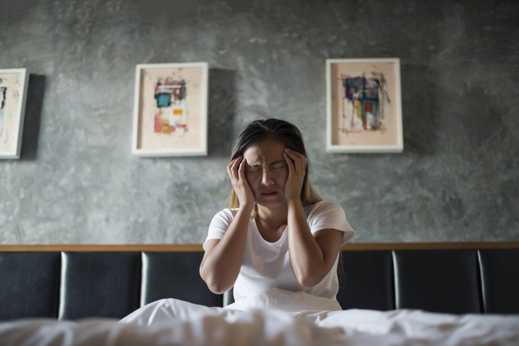 Donna che si tiene la testa in stato triste e depressivo