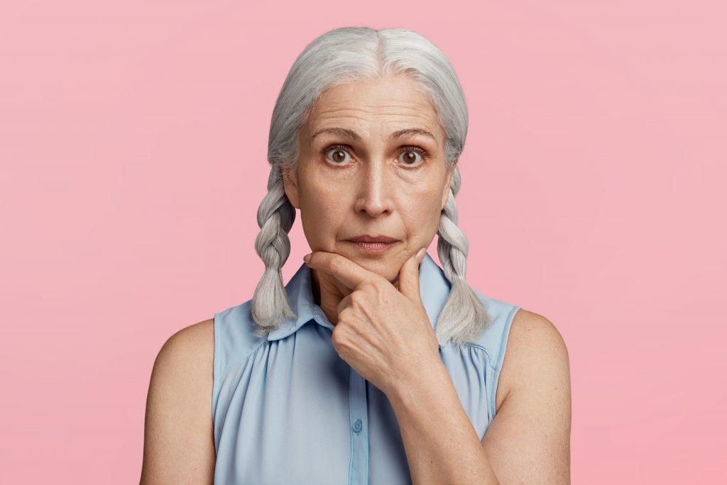 Donna anziana che pensa toccandosi il mento su sfondo rosa