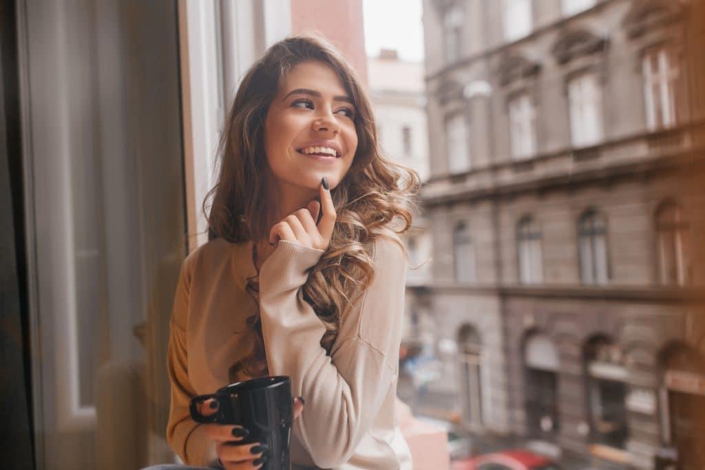 donna che si tocca il mento ridendo - mentoplastica
