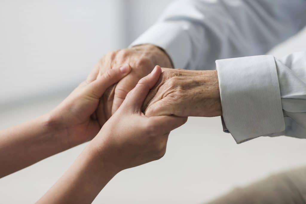 mani giovani che stringono mani più vecchie - ringiovanimento mani